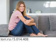 Купить «счастливая девушка сидит на сером диване в комнате», фото № 5014408, снято 7 апреля 2013 г. (c) Wavebreak Media / Фотобанк Лори
