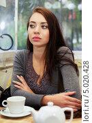 Купить «Молодая брюнетка сидит за столиком в кафе», фото № 5020428, снято 15 октября 2012 г. (c) Сергей Сухоруков / Фотобанк Лори