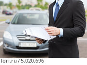 Мужчина с документами на фоне автомобиля. Стоковое фото, фотограф Syda Productions / Фотобанк Лори