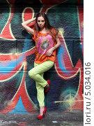 Юная девушка на городской улице позирует на фоне стены, расписанной граффити (2013 год). Редакционное фото, фотограф Игорь Долгов / Фотобанк Лори