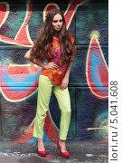Красивая длинноволосая девушка на городской улице позирует на фоне стены расписанной граффити. Стоковое фото, фотограф Игорь Долгов / Фотобанк Лори