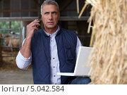 Купить «Фермер с ноутбуком возле стога сена», фото № 5042584, снято 28 сентября 2010 г. (c) Phovoir Images / Фотобанк Лори