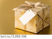 Купить «Новогодний подарок с биркой на золотом фоне», фото № 5059108, снято 21 августа 2013 г. (c) CandyBox Images / Фотобанк Лори