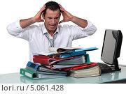 Купить «Офисный работник схватился за голову, заваленный бумажной работой», фото № 5061428, снято 10 марта 2011 г. (c) Phovoir Images / Фотобанк Лори