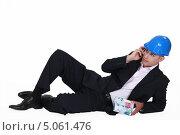 Купить «Мужчина в костюме и каске с домиком из банкнот в руке говорит по мобильному телефону», фото № 5061476, снято 11 апреля 2011 г. (c) Phovoir Images / Фотобанк Лори