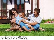 Купить «Семья играет с ребенком на лужайке перед домом», фото № 5070320, снято 6 июня 2013 г. (c) Raev Denis / Фотобанк Лори