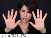 Купить «Девушка отталкивает зрителя ладонями», фото № 5081372, снято 21 марта 2011 г. (c) Phovoir Images / Фотобанк Лори