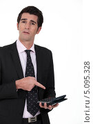 Купить «Бизнесмен указывает на калькулятор у себя в руке», фото № 5095328, снято 5 апреля 2011 г. (c) Phovoir Images / Фотобанк Лори