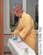 Купить «Девушка в бигуди гладит одежду», фото № 5096192, снято 25 сентября 2013 г. (c) Андрей Некрасов / Фотобанк Лори