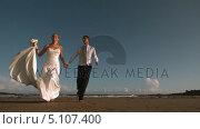 Купить «Cheerful bridal couple running on the beach», видеоролик № 5107400, снято 22 июля 2019 г. (c) Wavebreak Media / Фотобанк Лори