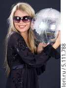 Купить «Девушка в черном коротком платье с диско-шаром на темном фоне», фото № 5111788, снято 26 июля 2008 г. (c) Syda Productions / Фотобанк Лори