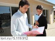 Купить «Улыбающийся клиент риэлтора читает документы на дом», фото № 5119912, снято 27 апреля 2010 г. (c) Phovoir Images / Фотобанк Лори