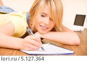 Юная девушка лежит на полу с блокнотом и ручкой. Стоковое фото, фотограф Syda Productions / Фотобанк Лори