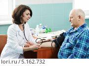 Купить «Молодая доктор меряет давление пожилому мужчине в медицинском кабинете», фото № 5162732, снято 12 марта 2013 г. (c) Дмитрий Калиновский / Фотобанк Лори