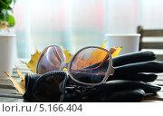 Женские перчатки, солнечные очки и желтые листья клена лежат на столе в кафе (2013 год). Редакционное фото, фотограф Илья Сладков / Фотобанк Лори
