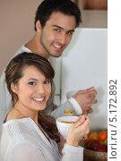 Купить «Девушка ест хлопья рядом с мужем», фото № 5172892, снято 11 марта 2010 г. (c) Phovoir Images / Фотобанк Лори