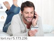 Купить «Мужчина лежит на животе и звонит по телефону», фото № 5173236, снято 17 мая 2010 г. (c) Phovoir Images / Фотобанк Лори