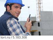 Купить «Улыбающийся рабочий с рацией на фоне стройки», фото № 5183308, снято 29 июля 2010 г. (c) Phovoir Images / Фотобанк Лори