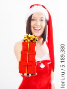 Купить «Девушка в красном платье и рождественском колпаке держит перед собой три подарочные коробки, перевязанные золотой лентой», фото № 5189380, снято 14 октября 2013 г. (c) Наталия Кленова / Фотобанк Лори