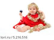 Малыш в новогодней мишуре сидит на белом фоне. Стоковое фото, фотограф Nikolay Kostochka / Фотобанк Лори