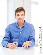 Купить «Молодой человек запивает лекарство водой», фото № 5222564, снято 3 октября 2013 г. (c) Syda Productions / Фотобанк Лори