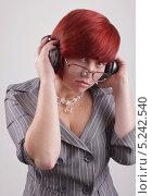 Симпатичная девушка в костюме увлеченно слушает музыку через большие наушники. Стоковое фото, фотограф Даниил Петров / Фотобанк Лори