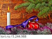 Новогодний шарик, горящая свеча и  мишура на фоне с еловыми ветками. Стоковое фото, фотограф Сергей Прокопенко / Фотобанк Лори