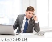 Купить «Бизнесмен в офисе разговаривает по телефону», фото № 5245824, снято 3 октября 2013 г. (c) Syda Productions / Фотобанк Лори
