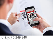 Купить «деловой мужчина сканирует QR-код», фото № 5249840, снято 6 июля 2013 г. (c) Андрей Попов / Фотобанк Лори