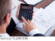 деловой человек что-то считает на калькуляторе, фото № 5249936, снято 6 июля 2013 г. (c) Андрей Попов / Фотобанк Лори
