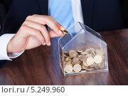 Купить «мужская рука бросает монету в копилку», фото № 5249960, снято 6 июля 2013 г. (c) Андрей Попов / Фотобанк Лори