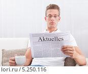 Купить «молодой мужчина в очках читает газету и пьет кофе», фото № 5250116, снято 6 июля 2013 г. (c) Андрей Попов / Фотобанк Лори