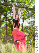 Купить «Веселая девушка в красной юбке повисла на ветке», фото № 5259804, снято 2 июня 2013 г. (c) Сергей Сухоруков / Фотобанк Лори