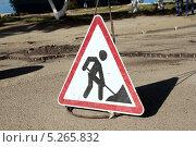 """Запрещающий знак """"идут дорожные работы, проезд закрыт"""" на фоне разбитой дороги - черный силуэт человека с лопатой на белом фоне. Стоковое фото, фотограф Елена Заммоева / Фотобанк Лори"""