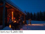 Купить «Друзья наслаждаются горячими напитками зимним вечером у деревенского домика», фото № 5269180, снято 26 января 2013 г. (c) CandyBox Images / Фотобанк Лори