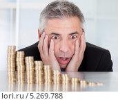 Купить «испуганный бизнесмен смотрит на уменьшающуюся прибыль», фото № 5269788, снято 7 апреля 2013 г. (c) Андрей Попов / Фотобанк Лори