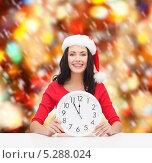 Купить «Счастливая девушка в шапке Санты смотрит на часы и ждет наступления полночи», фото № 5288024, снято 20 октября 2013 г. (c) Syda Productions / Фотобанк Лори