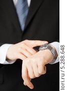Купить «Молодой бизнесмен в сорочке и галстуке смотрит на наручные часы», фото № 5288648, снято 3 апреля 2013 г. (c) Syda Productions / Фотобанк Лори