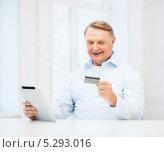 Купить «Пожилой мужчина в светлой рубашке с планшетным компьютером в руках», фото № 5293016, снято 12 октября 2013 г. (c) Syda Productions / Фотобанк Лори
