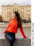 Симпатичная молодая девушка в оранжевой куртке сидит на каменном парапете набережной (2013 год). Стоковое фото, фотограф Юрий Селиванов / Фотобанк Лори