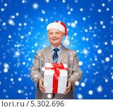 Купить «Мужчина в шапке Санты держит в руках новогодний подарок», фото № 5302696, снято 12 октября 2013 г. (c) Syda Productions / Фотобанк Лори