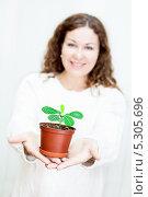Купить «Девушка с растением в горшочке на вытянутых руках. Фокус на растение», фото № 5305696, снято 17 ноября 2013 г. (c) Кекяляйнен Андрей / Фотобанк Лори