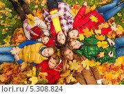Купить «Счастливые дети лежат на осенних листьях в парке», фото № 5308824, снято 6 октября 2013 г. (c) Сергей Новиков / Фотобанк Лори