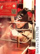 Купить «Мужчина делает гравировку на кружке. Рождественская ярмарка», фото № 5310768, снято 19 декабря 2012 г. (c) Мария Николаева / Фотобанк Лори