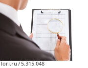 Купить «бизнесмен рассматривает документ через увеличительное стекло», фото № 5315048, снято 24 августа 2013 г. (c) Андрей Попов / Фотобанк Лори