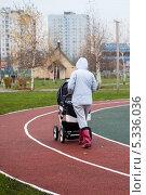 Купить «Молодая мама катит коляску с младенцем», эксклюзивное фото № 5336036, снято 6 ноября 2013 г. (c) Родион Власов / Фотобанк Лори