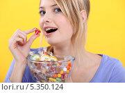 Купить «Девушка ест мармелад», фото № 5350124, снято 13 января 2011 г. (c) Phovoir Images / Фотобанк Лори