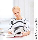Купить «улыбающаяся студентка листает учебник за столом», фото № 5352816, снято 17 октября 2013 г. (c) Syda Productions / Фотобанк Лори