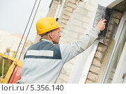 Купить «Рабочий штукатурит фасад здания», фото № 5356140, снято 3 октября 2011 г. (c) Дмитрий Калиновский / Фотобанк Лори