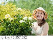 Купить «Веселая женщина в панаме стоит у цветущих роз в саду», фото № 5357552, снято 29 мая 2011 г. (c) Яков Филимонов / Фотобанк Лори